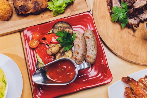 Mesa de jantar com uma variedade de lanches e saladas. salmão, azeitonas, vinho, legumes, torradas de peixe grelhado. o conceito de um jantar de comemoração em família.