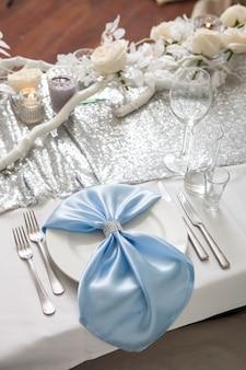 Mesa de jantar de casamento fechar. decoração com flores e velas. prato com guardanapo azul decorado com jóias em cima da mesa festiva