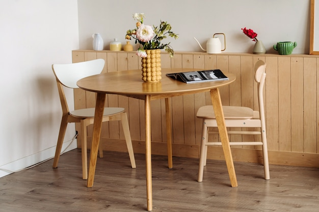 Mesa de jantar de madeira em um interior brilhante em casa. em cima da mesa estão peônias em um vaso amarelo de grife.