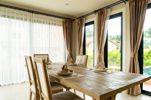 Mesa de jantar de madeira em uma sala com cortina e janela