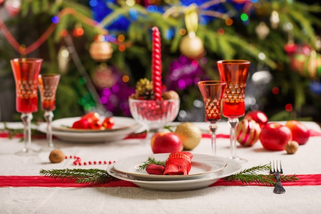 Mesa de jantar de natal decorada com árvore de natal no fundo