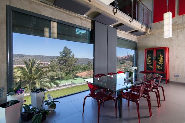 Mesa de jantar de vidro com cadeiras de metacrilato vermelho, interior da casa moderna com orquídeas. casa de concreto de altura dupla. com vista para o campo