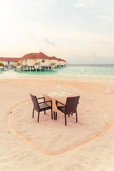 Mesa de jantar e cadeira na praia com vista para o mar fundo nas maldivas