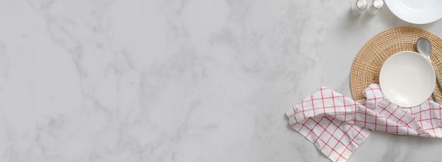 Mesa de jantar em mármore com placas de cerâmica brancas no espaço individual, talheres, garrafas de tempero, guardanapo e espaço para texto