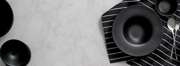 Mesa de jantar em mármore com utensílios de cozinha em cerâmica preta, talheres no espaço guardanapo e cópia
