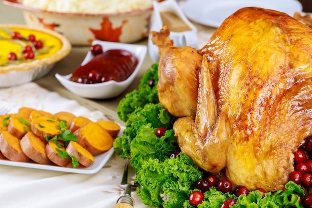 Mesa de jantar festiva servida com peru, decorada com couve e cranberry.