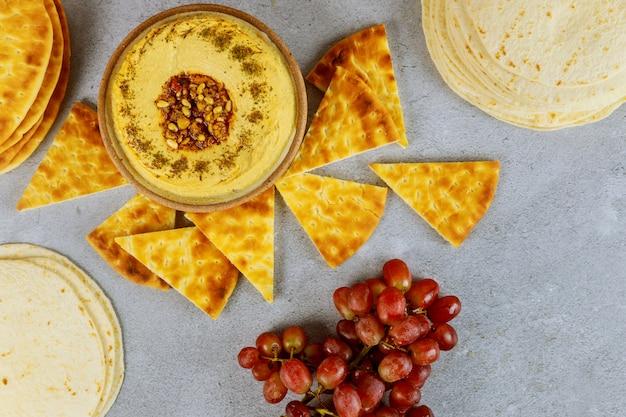 Mesa de jantar judaica com pão pita, hummus e uvas.