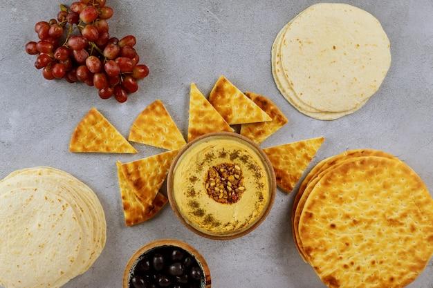 Mesa de jantar libanesa com pão pita, hummus e azeitonas