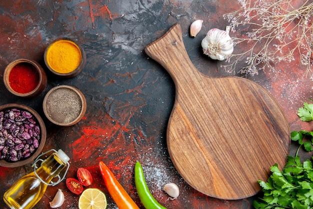 Mesa de jantar, placa de corte de grãos de garrafa de óleo caídos e especiarias diferentes na mesa de cores misturadas