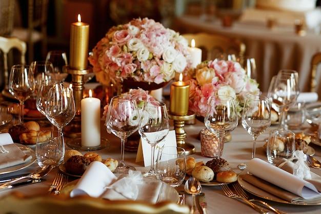 Mesa de jantar rica servida em tons rosa e dourados