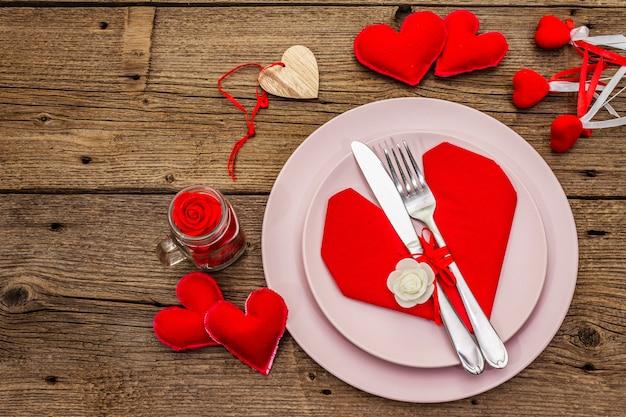 Mesa de jantar romântica com pratos e guardanapo em forma de coração