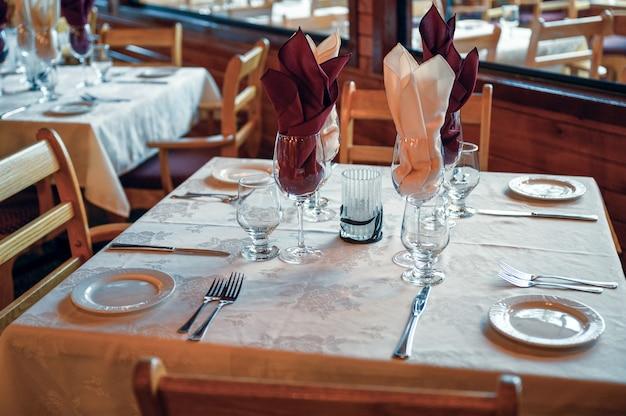 Mesa de jantar rústica de madeira com talheres e copos em restaurante