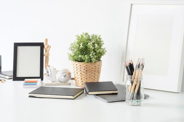 Mesa de local de trabalho do artista com pote de lápis, caderno de desenho, moldura e planta