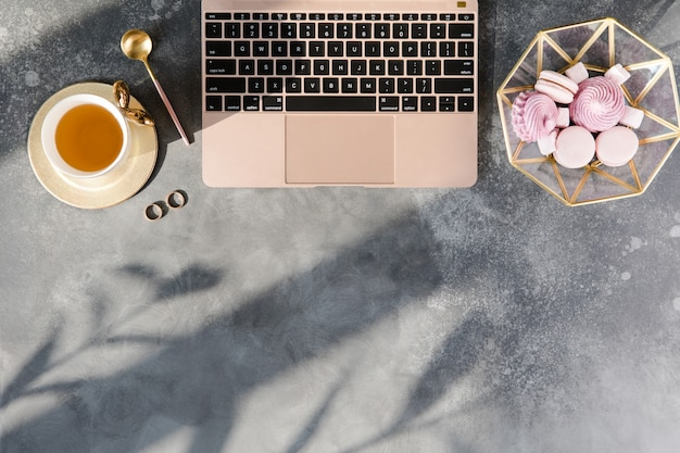Mesa de loft moderno escritório em casa. espaço de trabalho com caderno rosa pastel, chá e decorações em fundo cinza