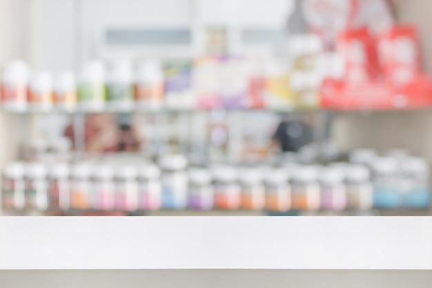 Mesa de loja de farmácia com remédios desfocados nas prateleiras ao fundo da farmácia