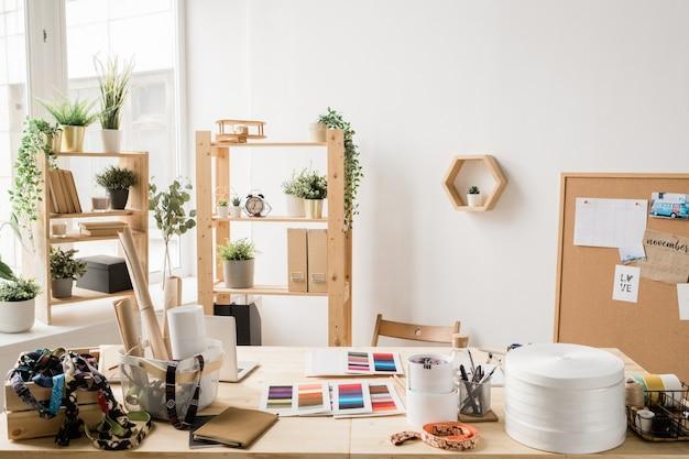 Mesa de madeira à janela com vários materiais para o trabalho criativo de designer de moda ou de interiores em um estúdio ou escritório moderno
