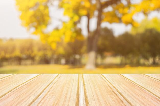 Mesa de madeira amarela vazia com parque da cidade turva