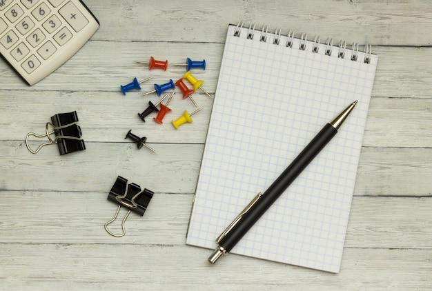 Mesa de madeira, bloco de notas, caneta esferográfica, calculadora, plano de fundo
