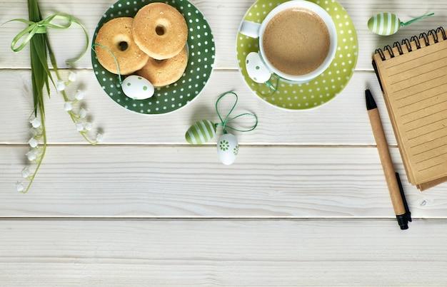 Mesa de madeira branca com café expresso, biscoitos, bloco de notas, ovos de páscoa e flores da primavera, espaço