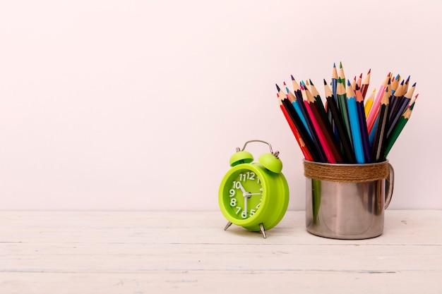 Mesa de madeira branca com despertador e lápis coloridos em branco