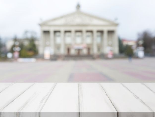 Mesa de madeira branca na frente da fachada do edifício público clássico turva
