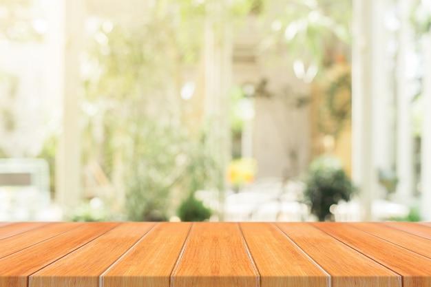 Mesa de madeira cheia de mesa vazia no fundo borrado do café.