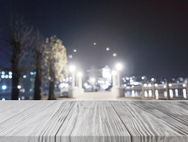 Mesa de madeira cinza na frente da cidade iluminada à noite