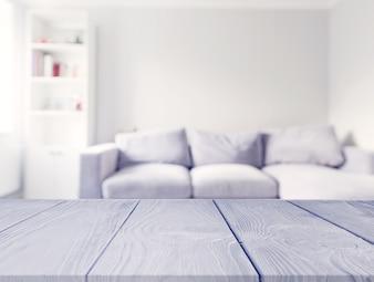 Mesa de madeira cinza na frente do sofá branco borrão na sala de estar