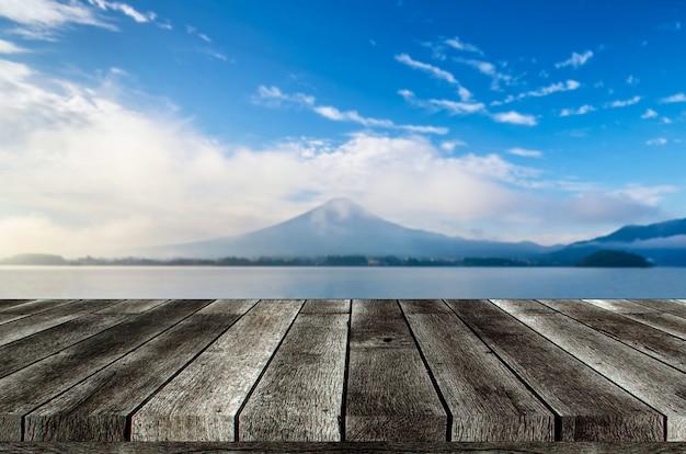 Mesa de madeira cinza vazia ou terraço de madeira com bela vista da montanha fuji com céu azul no início da manhã