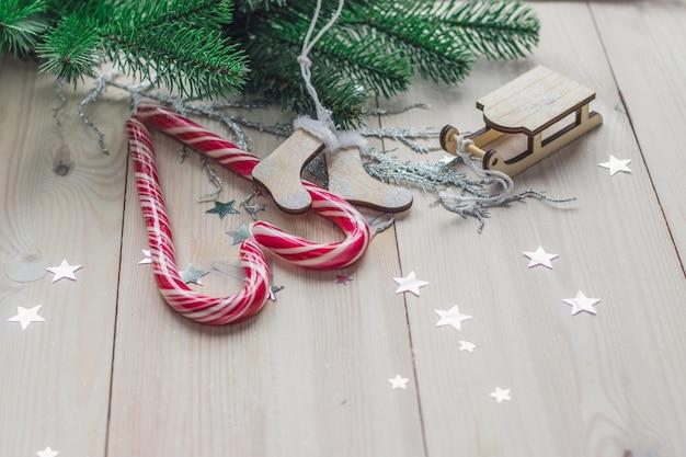 Mesa de madeira coberta com bastões de doces e enfeites de natal sob as luzes