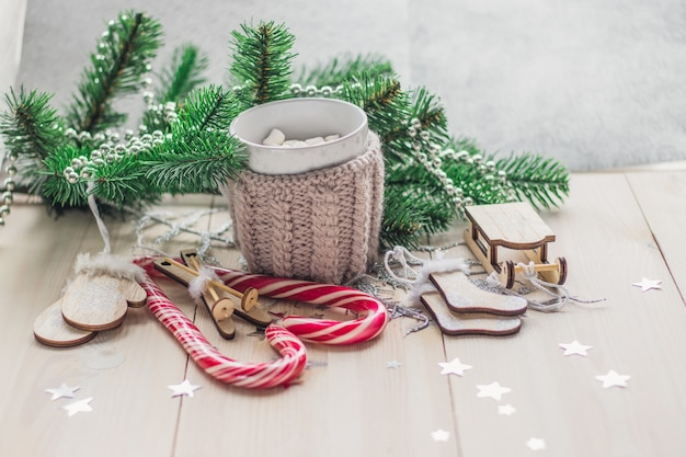 Mesa de madeira coberta com marshmallows de bastões de doces e decorações de natal sob as luzes
