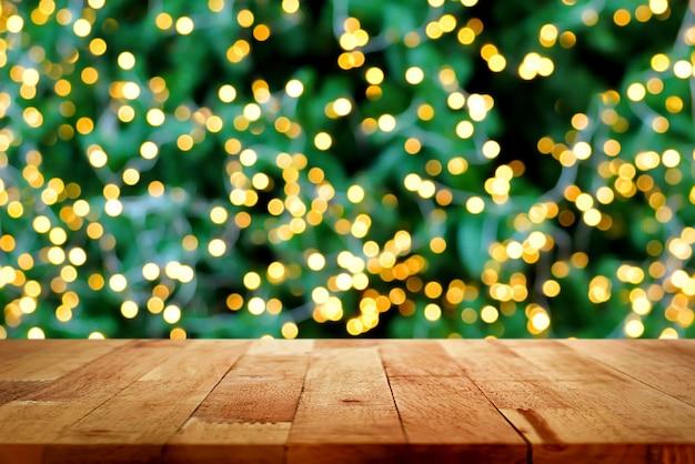 Mesa de madeira com bokeh de luz decorativa na árvore de natal no fundo