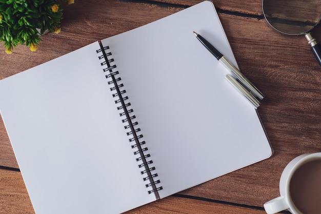 Mesa de madeira com caderno, lupa, caneta, plantas decorativas. vista superior com espaço de cópia, postura plana.