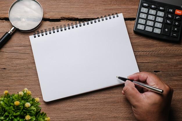 Mesa de madeira com caderno, óculos, lupa, caneta, plantas decorativas. vista superior com espaço de cópia, postura plana.