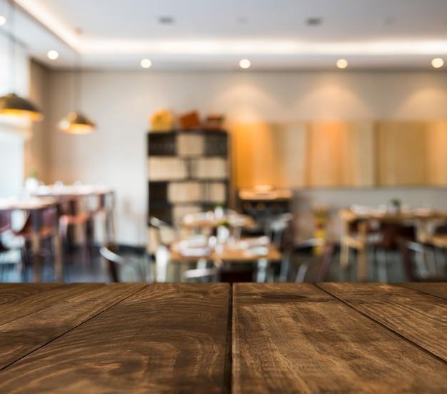 Mesa de madeira com cena de restaurante turva