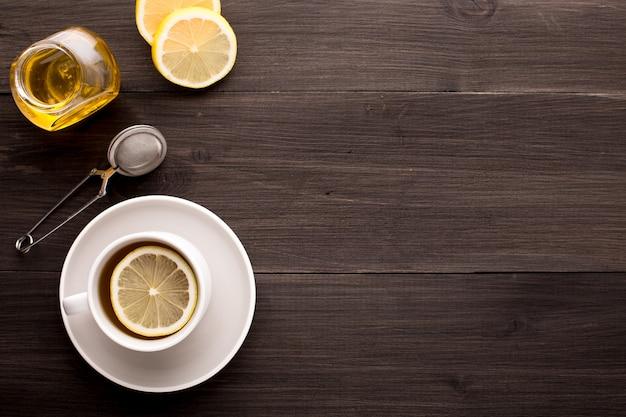 Mesa de madeira com chá preto, limão e mel