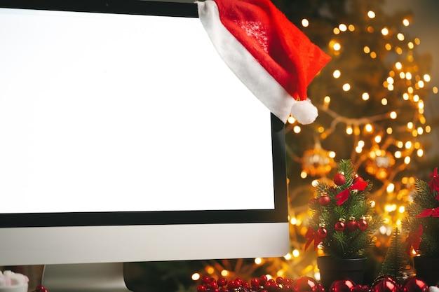 Mesa de madeira com computador com tela em branco e fundo desfocado com luzes de natal