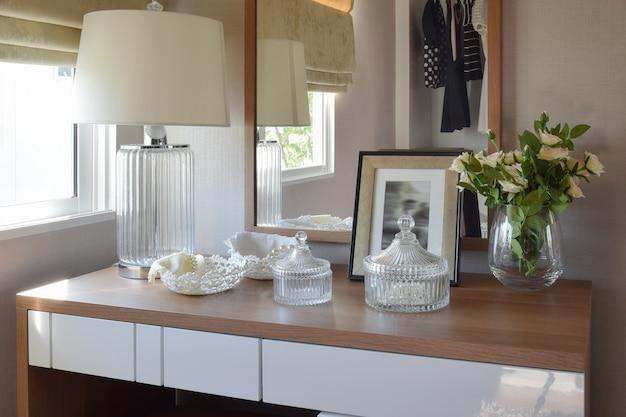 Mesa de madeira com conjunto de jóias, espelho, lâmpada no camarim