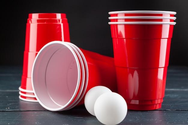 Mesa de madeira com copos vermelhos e bola para pong de cerveja