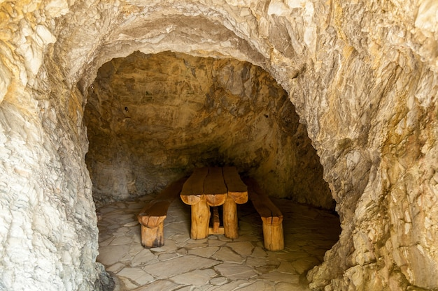 Mesa de madeira com dois bancos em sala de pedra. salas de pedra da geórgia. viagem à geórgia