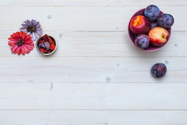 Mesa de madeira com frutas frescas e flores, ameixas e nectarinas com espaço para seu texto