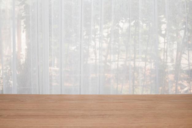 Mesa de madeira com fundo de janelas de cortina branca.
