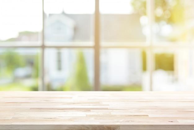 Mesa de madeira com janela e sol da manhã no fundo