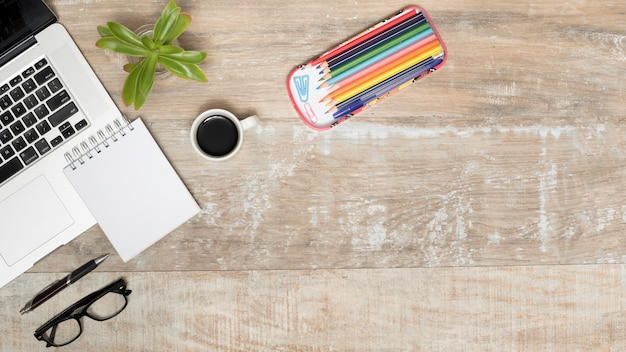 Mesa de madeira com laptop aberto; chá; óculos; caneta; planta e lápis coloridos