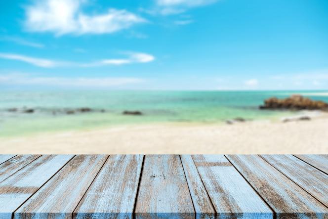 Mesa de madeira com mar natural turva de praia tropical e céu azul, fundo de férias de verão