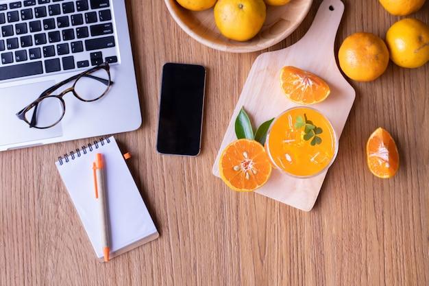 Mesa de madeira com mesa de escritório com copo de suco de laranja e smartphone de tela em branco.