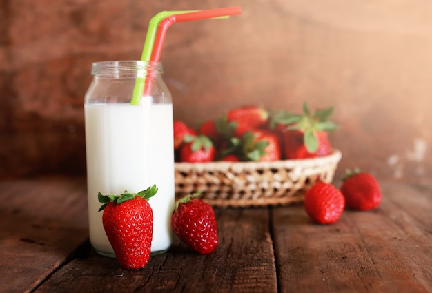 Mesa de madeira com morangos e leite em um copo