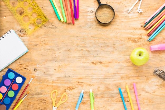 Mesa de madeira com objetos coloridos ao redor