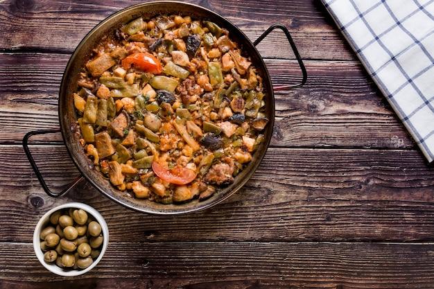Mesa de madeira com paella e azeitonas verdes comida caseira tradicional. paella com legumes