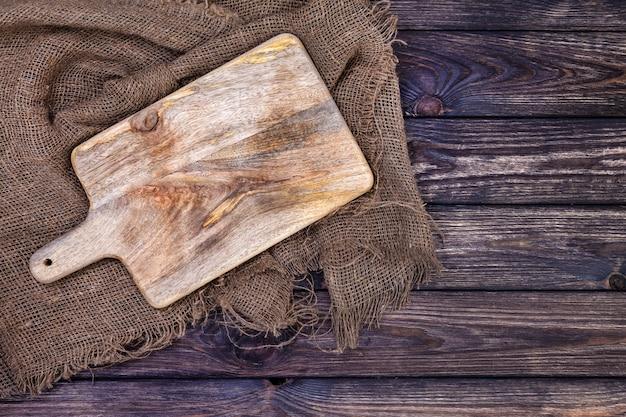 Mesa de madeira com pano de estopa e tábua